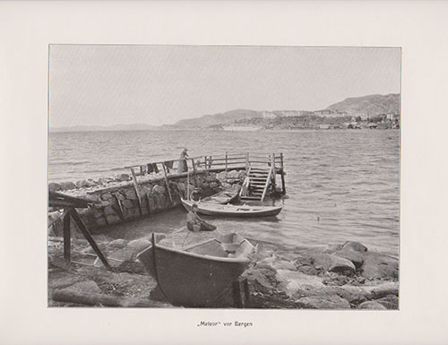 The S.S. Meteor in the distant background near the harbor of Bergen. A man shown fishing by the shore with a woman standing on the docks.