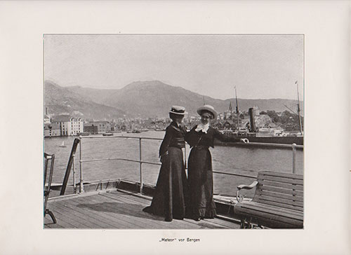 The S.S. Meteor is in the very distant background. Two well-dressed women converse on the pier in the harbor of Bergen, Norway.