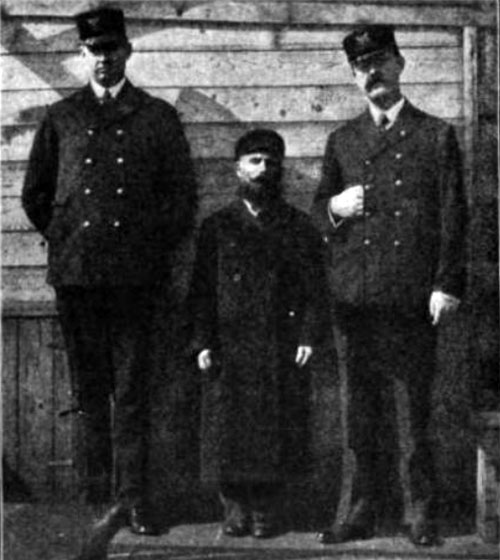 Photo 09 - An Immigrant Standing With Ellis Island Inspectors