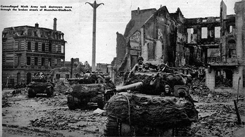 Camouflaged Ninth Army Tank Destroyers move through the broken streets of Muenchen-Gladbach