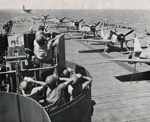 ON THE ALERT—Carrier men scan sky as F6F Hellcats line flight deck in WW II.
