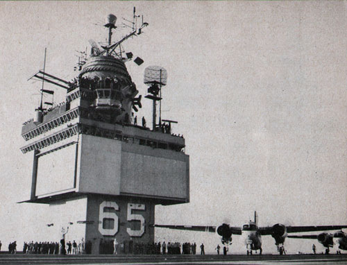 Crew members watch carrier's first aircraft launching.