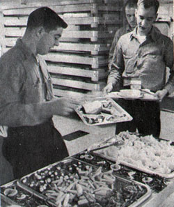 Carrier crewmen help themselves to food