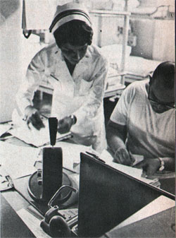 Navy nurse Hill checks patients' medical records with corpsman.