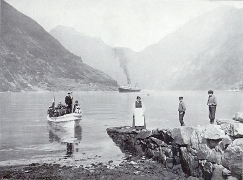 Photo 091: The S.S. Auguste Victoria in Merok, Geiranger Fjord, Norway - A tender is arriving with load of passengers.