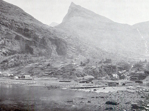 Photo 102: View of the village of Merok as seen from across the Fjord. Visable are a number of farm buildings, Church and the village of Merok on the far right side.