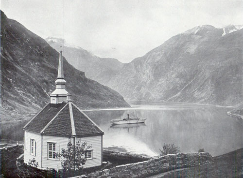 Photo 095: The S.S. Meteor in Geiranger Fjord with view of Stave Church in the foreground.