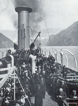 Photo 096: The SS Meteor in Geiranger Fjord view of immigrants and tourist passengers on deck.
