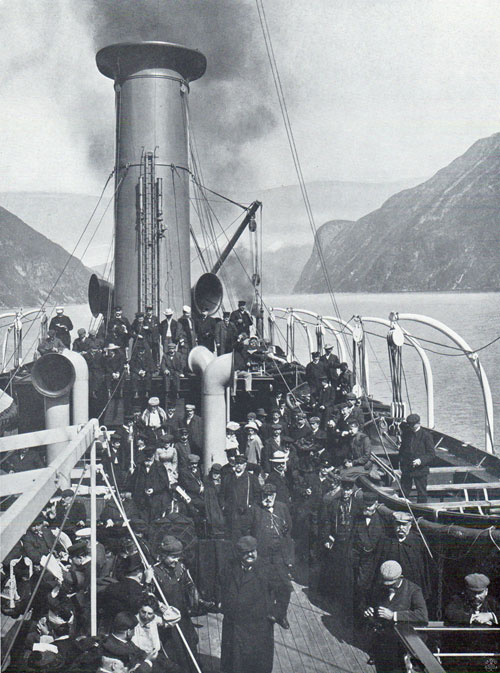 Photo 096: The S.S. Meteor in Geiranger Fjord view of immigrants and tourist passengers on deck.