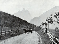 Photo 047: Morning in Romsdal Horn. Scene depicts a traditional mode of transportation, the Stolkjaerre or two wheeled, horse-drawn buggie, a common sight throughout Norway.