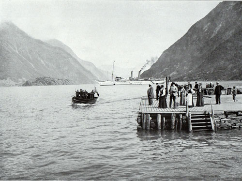 Photo 030: The S.S. Prinzessin Victoria Luise at Odda. People, possibly immigrants waiting at the pier for the tender to arrive from the steamer.