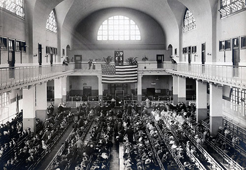 Immigrants Seated on Long Benches in the Main Hall at Ellis Island.