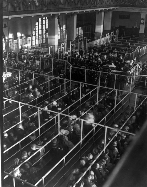 Emigrants in 'pens' at Ellis Island, New York, probably on or near Christmas --note the decorations