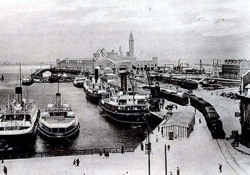 Steamships Docked at the Landing Stage at Cherbourg-Octeville. Train Station is in the Far Background.